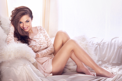 Fashion photo of beautiful young sexy woman wearing lace dress, relaxing and smiling in bright room, on the white couch. Looking at camera.