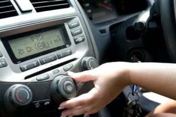 adjusting-the-volume-of-her-car-radio-while-seated-behind-the-wheel-of-her-automobile-725x482