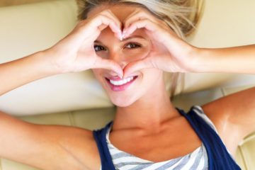 An attractive woman lying on sofa looking through a heart sign formed by her hand