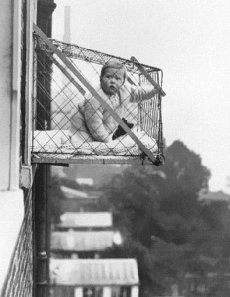 Dieťa v klietke, ktorá sa bežne používala, aby mali bytovkové deti dostatok slnka a vzduchu, 1937