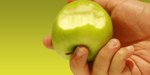 9554-a-hand-holding-a-bitten-green-apple-pv