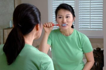 17067-an-asian-woman-brushing-her-teeth-in-a-mirror-pv